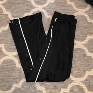 Svarta wct byxor med revärer och knäppning längs hela byxbenet. (Trackpants) Storlek S men har dragsko i midjan så passar även XS. För långa för mig som är 155cm