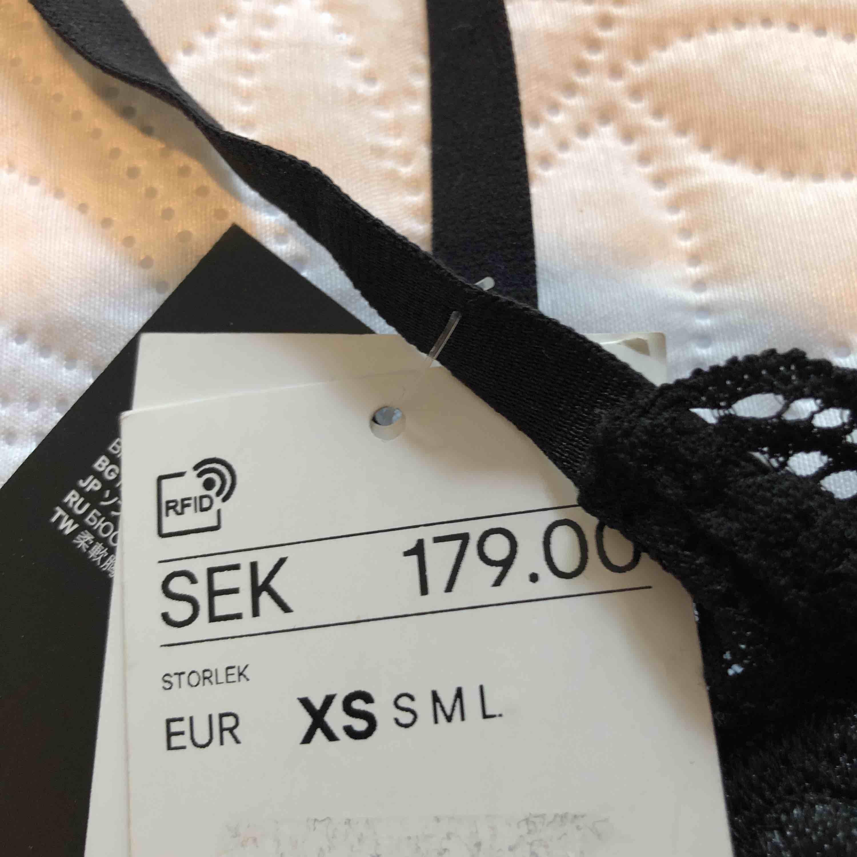 Fin bygellös bh från H&M i siden med svart spets och svarta broderade rosor. Helt ny och oanvänd, köpt för 179kr. Accessoarer.