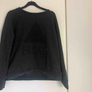"""Tröja från Lager 157. Svart triangel med texten """"EQUAL"""" på framsidan, syns knappt"""