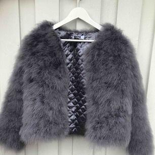 En grå fuskpäls jacka från Dennis Maglic. Använd några få gånger så i fint skick. Köparen står för frakten.
