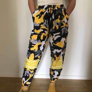 Gula camouflage byxor i nylon liknande material. Står i byxorna att de är M men köpte de i S och det sitter som S. Frakt ingår i priset! 🥰