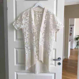 """Vit """"kimono"""" med långa fransar och genomskinligt tyg."""
