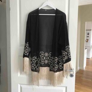 """Svart lite genomskinlig """"kimono"""" med beigea detaljer och fransar. Köpt på nätet, kommer ej ihåg märke."""