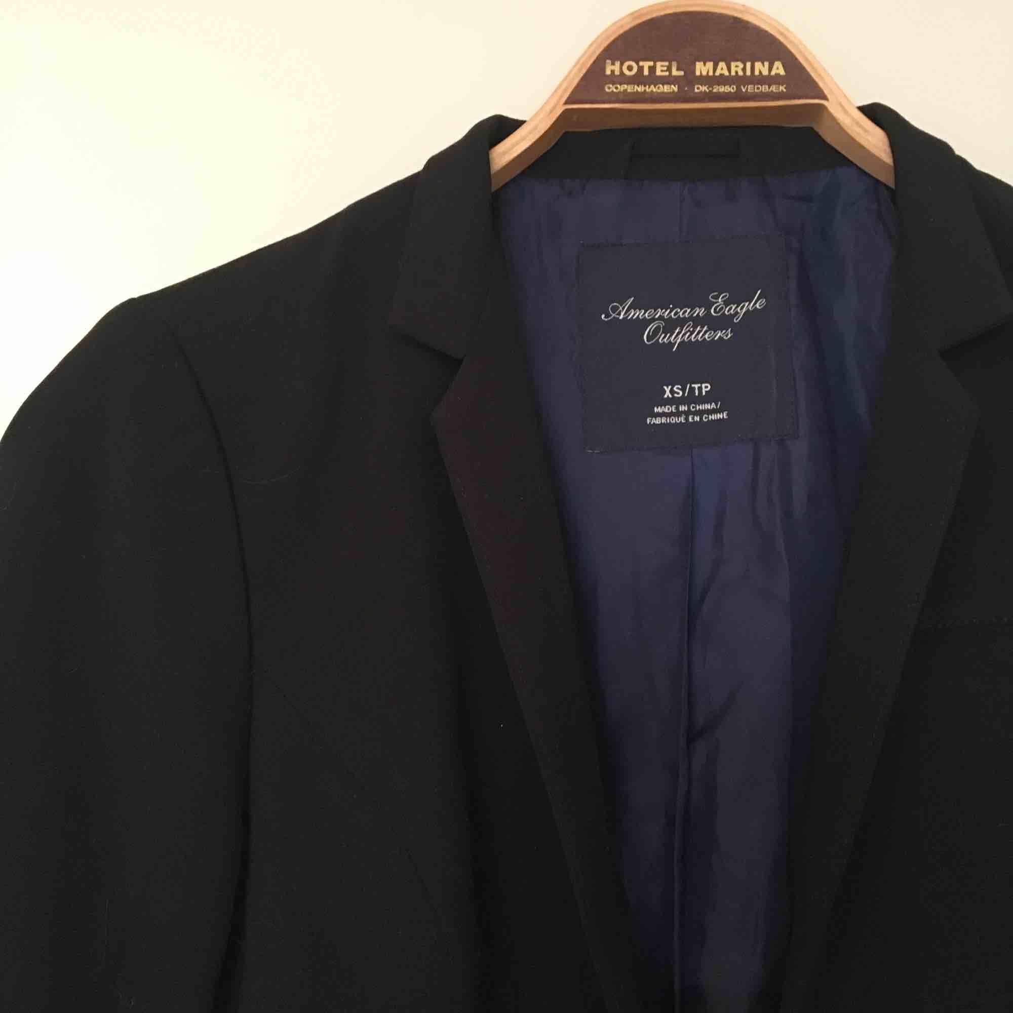 Kavaj, som når till midjan, mörkblått glänsande tyg inuti, går att stänga eller ha uppknäppt. 3 fickor😄. Kostymer.