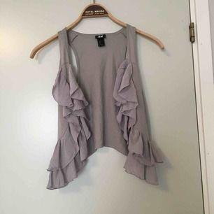 Sommrig väst med tunna volanger, i gråa toner. Passar perfekt om man vill göra en tshirt eller klänning mer festlig eller över en skjorta!