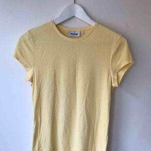 Gul T-Shirt från Weekday, aldrig använd så helt ny. Går att hämta på Södermalm annars tillkommer frakt på 50 kr.