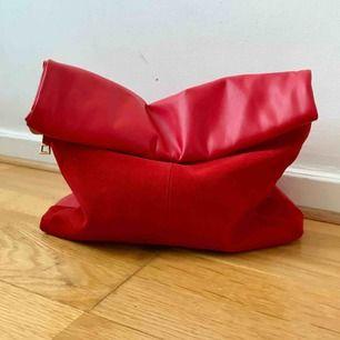 Röd väska clutch påsväska i mocka och läder. Använd en gång. Går bra att hämta på Södermalm annars kostar frakt 50 kr.