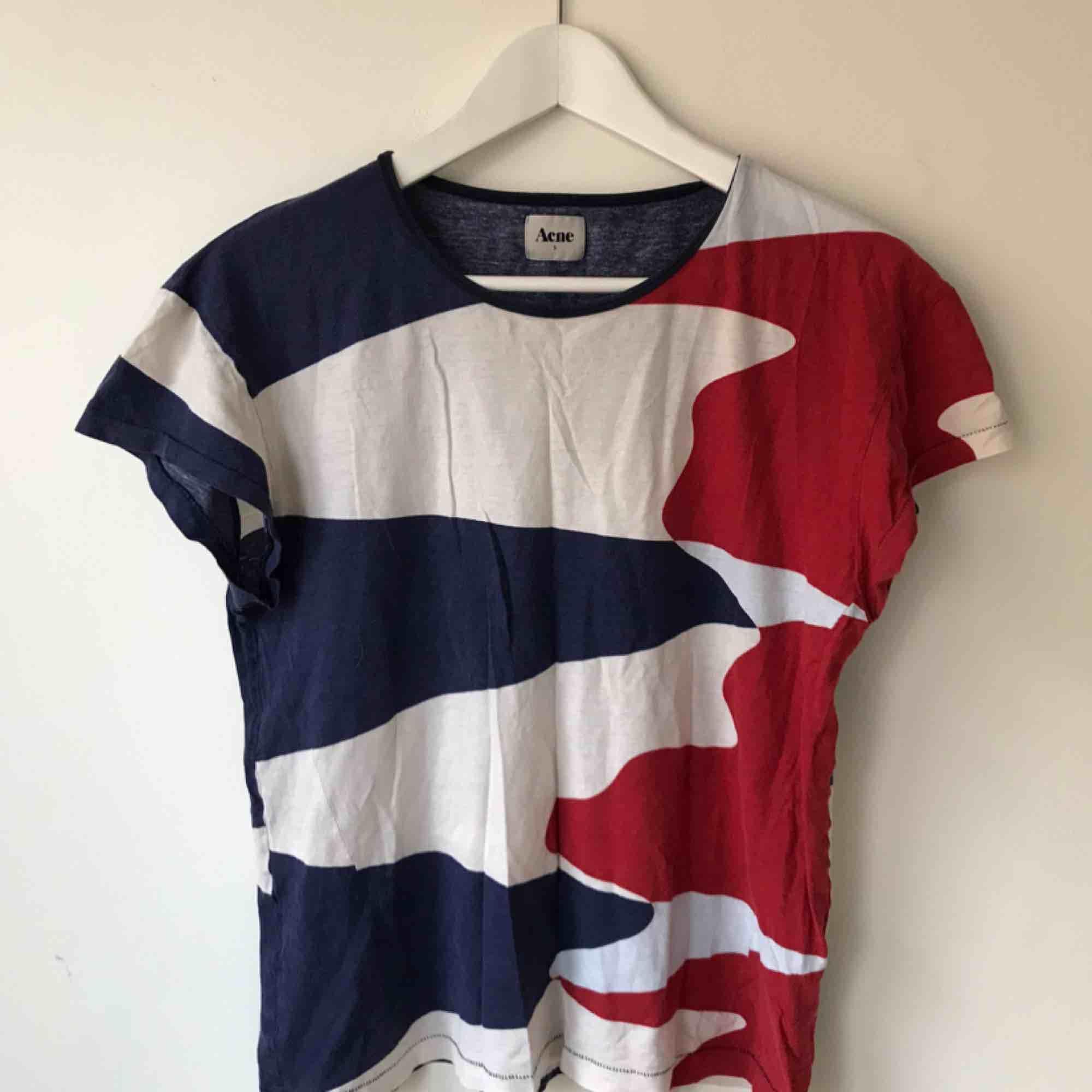 Acne T Shirt i röd/blått - välanvänd så säljs i befintligt skick. Går bra att hämta på Södermalm annars kostar frakt 50 kr. . T-shirts.