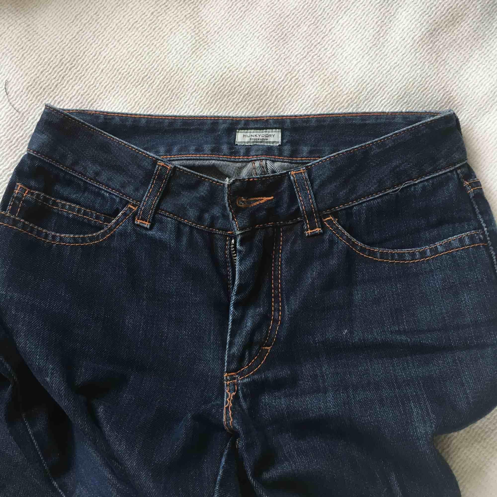 Ett par mörkablåa jeans. De är inte bootcut men de är inte helt lösa längst smalbenen. De är ganska långa, själv behöver jag vika upp dem. De går ungefär till ovanför naveln.. Jeans & Byxor.