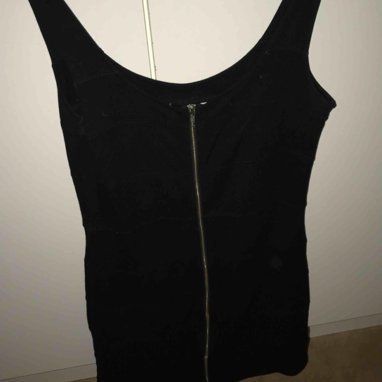 Svart klänning med en fungerande dragkedja hela vägen framtill. Aldrig använd. Frakt ingår i priset. Klänningar.