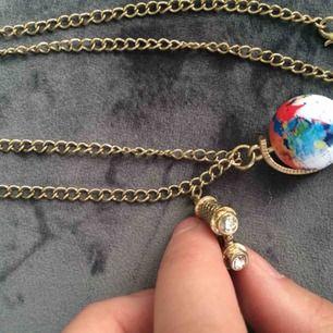 Halsband med jordglob (som snurrar) och kikare