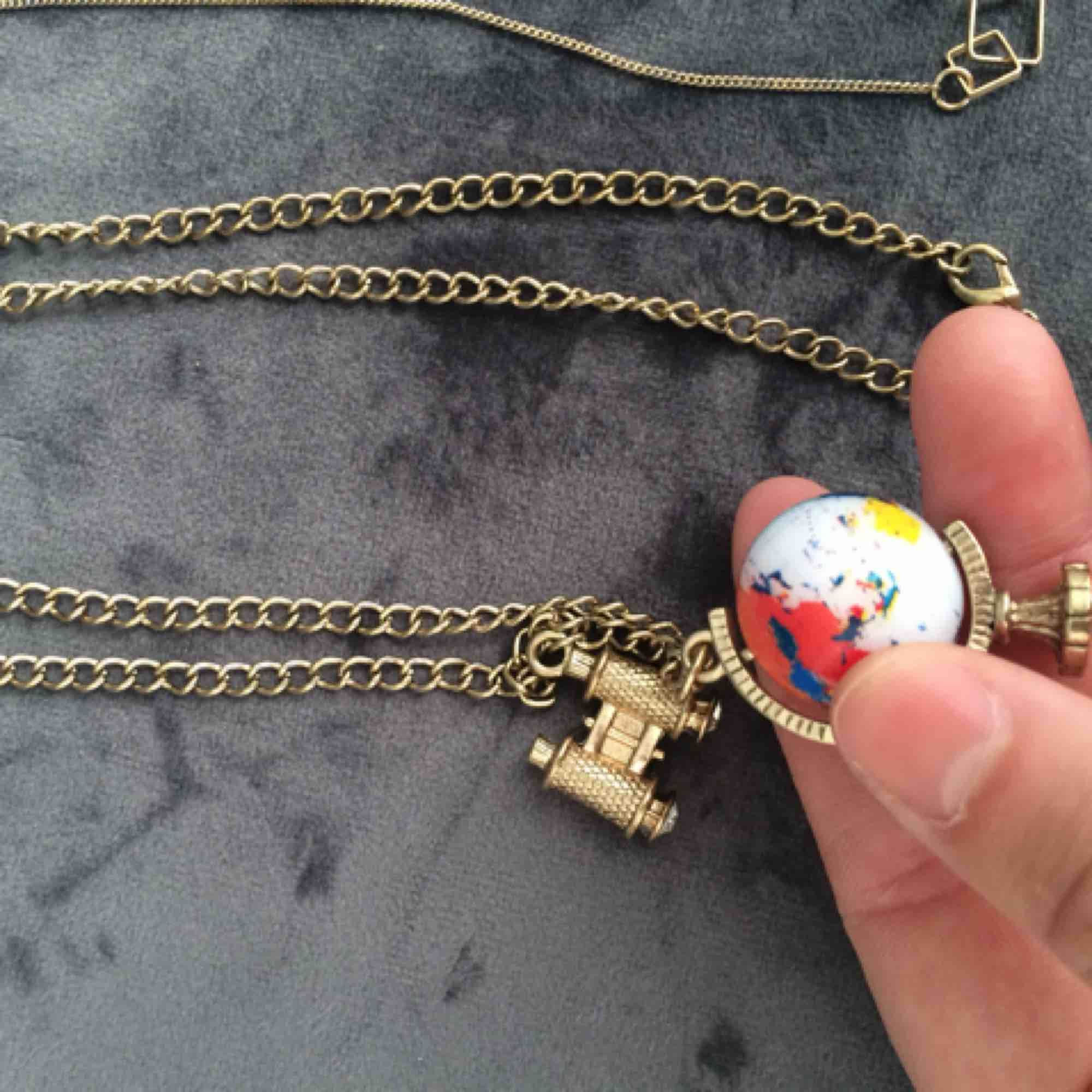 Halsband med jordglob (som snurrar) och kikare. Accessoarer.
