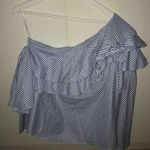 En tröja med volanger. En arm är off shoulder. Använd 1 gång. Frakt ingår i priset.