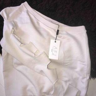 Säljer helt ny one shoulder tröja från AFJxNAKD! Aldrig använd, lappen sitter kvar!