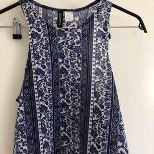 Kort linne med blått mönster. Använd 3-4 ggr, köptes för ca 2 år sedan på H&M. Säljer pga använder inte