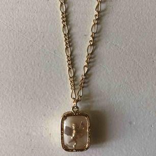 Guldhalsband från ASOS. Aldrig använt och i väldigt bra skick. Storleken kan anpassas alltifrån så smycket är i halsgropen eller en längre kedja på bröstet. Smycket är en guldängel med diamanter på inuti genomskinlig plast.
