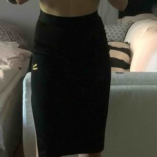 Puma x Kenza kjol. Aldrig använd, helt ny och superfin! Stretchigt, glansigt material och bred resår som markerar midjan. Liten slits på vänster sida. Midja: 30cm. Längd: 68cm.