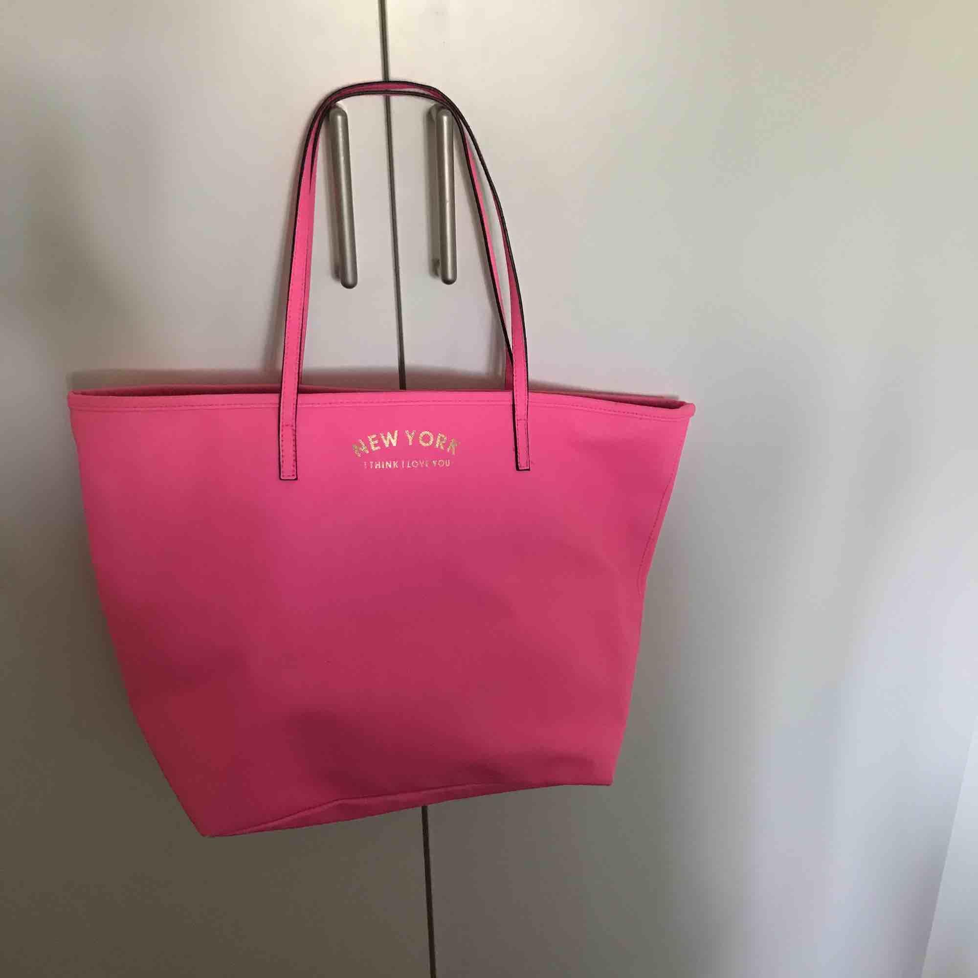 """Jättesnygg väska från H&M. Fin rosa färg med en guldig test """" NEW YORK - I THINK I LIVE YOU"""". På insidan är det ett fint mäster. Väskan är använd en gång för test. Det går att pruta om båda är överens. . Väskor."""