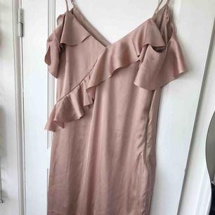 Fin ljusrosa glansig klänning från hm endast testad. Axelband samt volanger som går ner över axeln och ner på armen. Finns några fläckar eller liknande se sista bilden. Har tvättat den med handtvättmedel men verkar inte försvinna. Inkl frakt