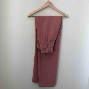 Rosa högmidjade kostymbyxor med knytning i midjan. Avända 2 gånger så i princip nyskick<3 Kan mötas upp längst roslagsbanan eller i stockholm, annars står köparen för frakt.