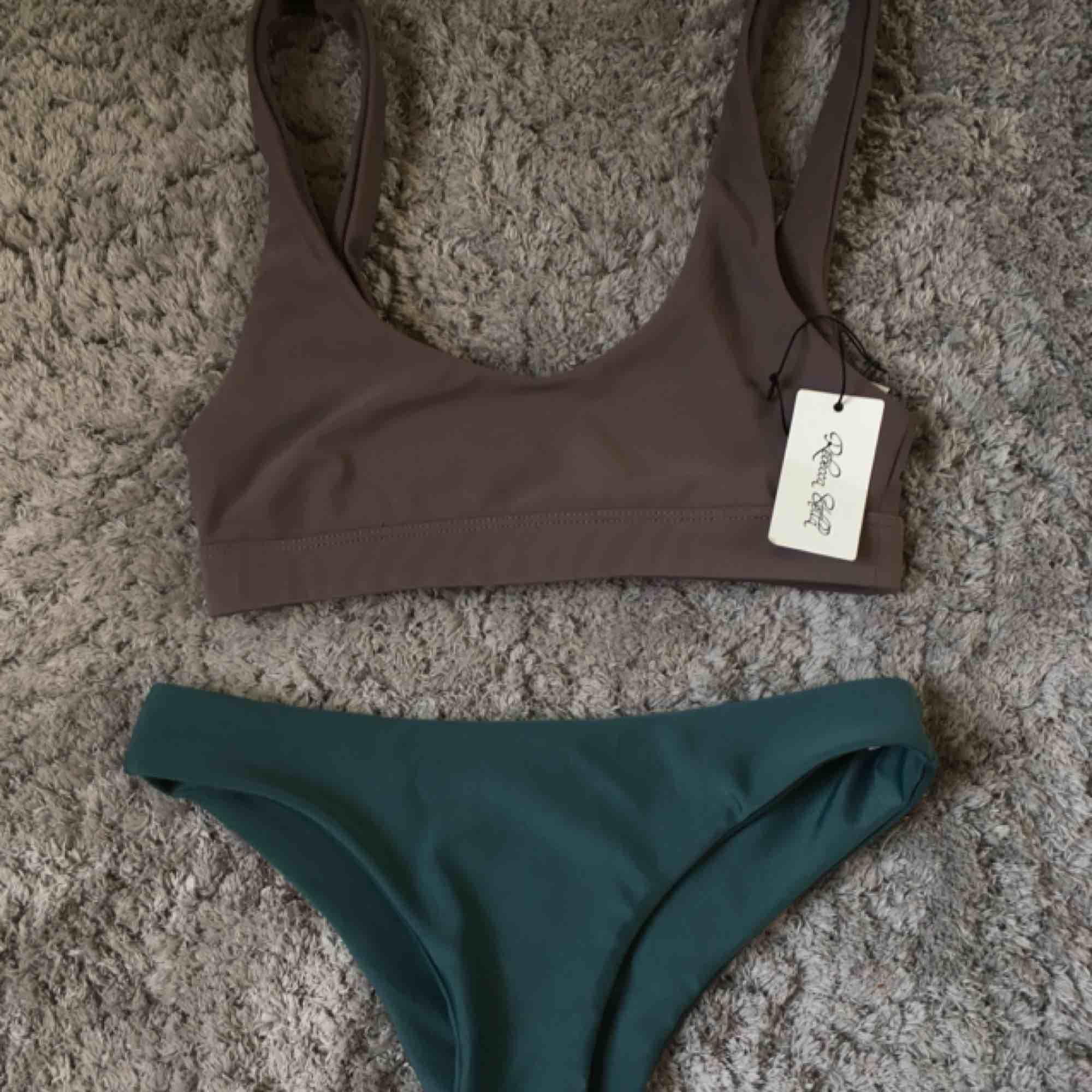 """Helt nya oanvända bikinis från na-kd. Den i färgen """"mud"""" är ifrån Rebecca Stella och den gröna köptes utan prislapp. Såååååå fina men är tyvärr försmå. Sömmarna är sydda inåt så d blir nästan utan sömmar vilket är jätte snyggt och ser lyxigare ut!. Övrigt."""