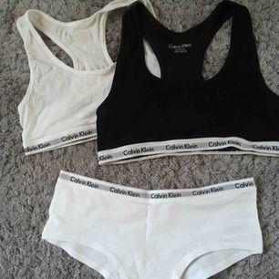 """Jätte fina underkläder ifrån Calvin Klein. De vita trosorna är aldrig använda, den vita toppen är använd någon enstaka gång, den svarta max 5 ggr! Inga defekter vad jag kan se förut en liten """"uttöjning""""på den svarta i respekt (se bild 2)."""