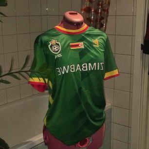 Snygg fotbollströja från Zimbabwe i sportigt andningsmatrial. Sitter lite baggy på mig som har XS/S och aldrig använd.
