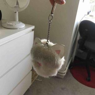 Gullig vit boll som man kan hänga på nyckeln eller väska. På bilderna ser den smutsig ut men den är nästan aldrig använd. Kan pruta lite!