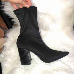 Boots med spetsig tå i stretch material, tyget är glansigt med svagt randig matt klack  Frakt tillkommer