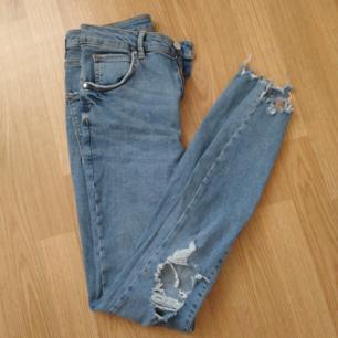 Stretchiga jeans med slitna detaljer vid knän och benslut. Fint skick. Betalas med swish (+ frakt)