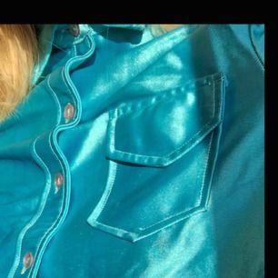 Neonblå skjorta i glansigt material. Frakt ingår!