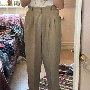 Väldigt fina beigea hipstriga kostymbyxor, köpta på beyond retro i Zinkensdamm för 300kr sommaren 2018. Använda ca 3 gånger av mig och jag skulle säga att det är i bra skick. Jag står inte för frakt