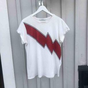 Nypris:500kr T-shirt från märket Gestuz med en röd glittrig blixt över bröstet. Använd fåtal gånger. Liten fläck, men syns knappt   Köpare står för frakt