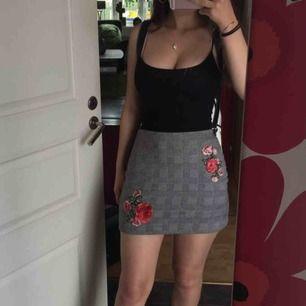 Rutig kjol med blommor på, aldrig använd. Så gott som ny. Köpt för något år sen.
