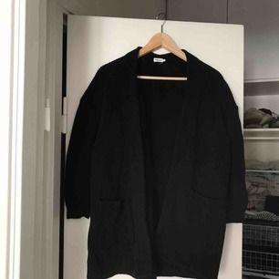 Mörkblå kofta från Filippa K. Går att använda såväl som kofta på vinter som jacka på sommaren. Fickor på sidan och bälte i midjan så det är en knytkofta!