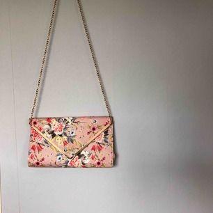 Rosa väska med blommor på och guldiga detaljer. Kan även användas som kuvertväsk! Jättefin till bal eller liknande. Köparen står för frakten.