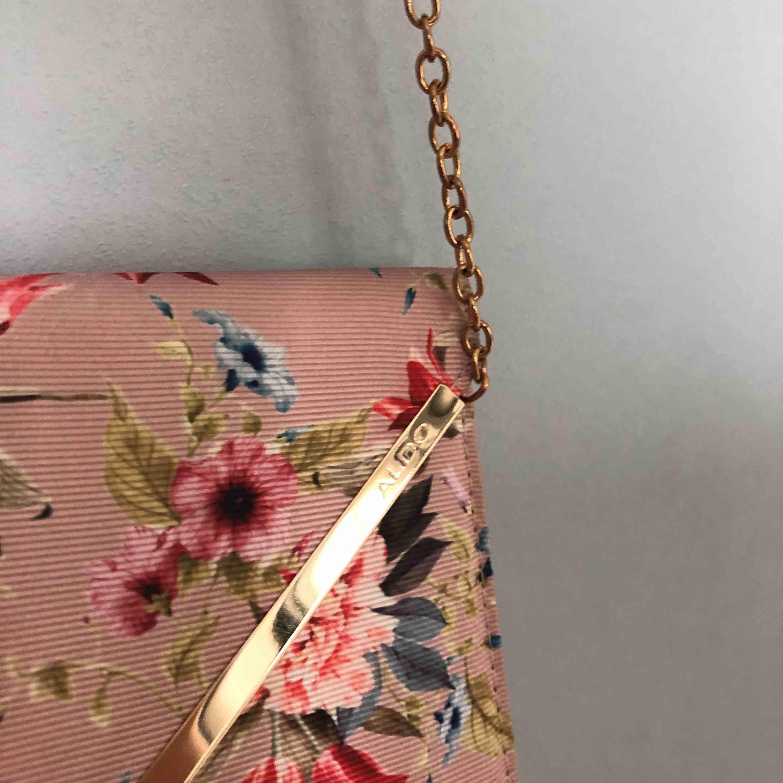 Rosa väska med blommor på och guldiga detaljer. Kan även användas som kuvertväsk! Jättefin till bal eller liknande. Köparen står för frakten.. Väskor.