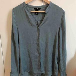 Turkos mönstrad blus med knappar från H&M, stl 34.