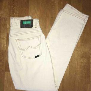 Vita jeans med bruna sömmar. Längden är ungefär 30,32 och modellen påminner om levis 501