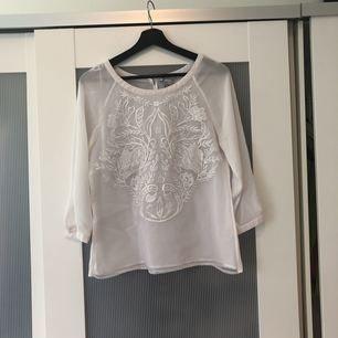 Kæmpe hvid bluse fra HM. Har et stort broderimønster på forsiden. Gennemsigtig ryg og arme.