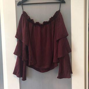 Flot rødvinbluse med flæser. Syk flot til et par sorte strikke jeans eller shorts.