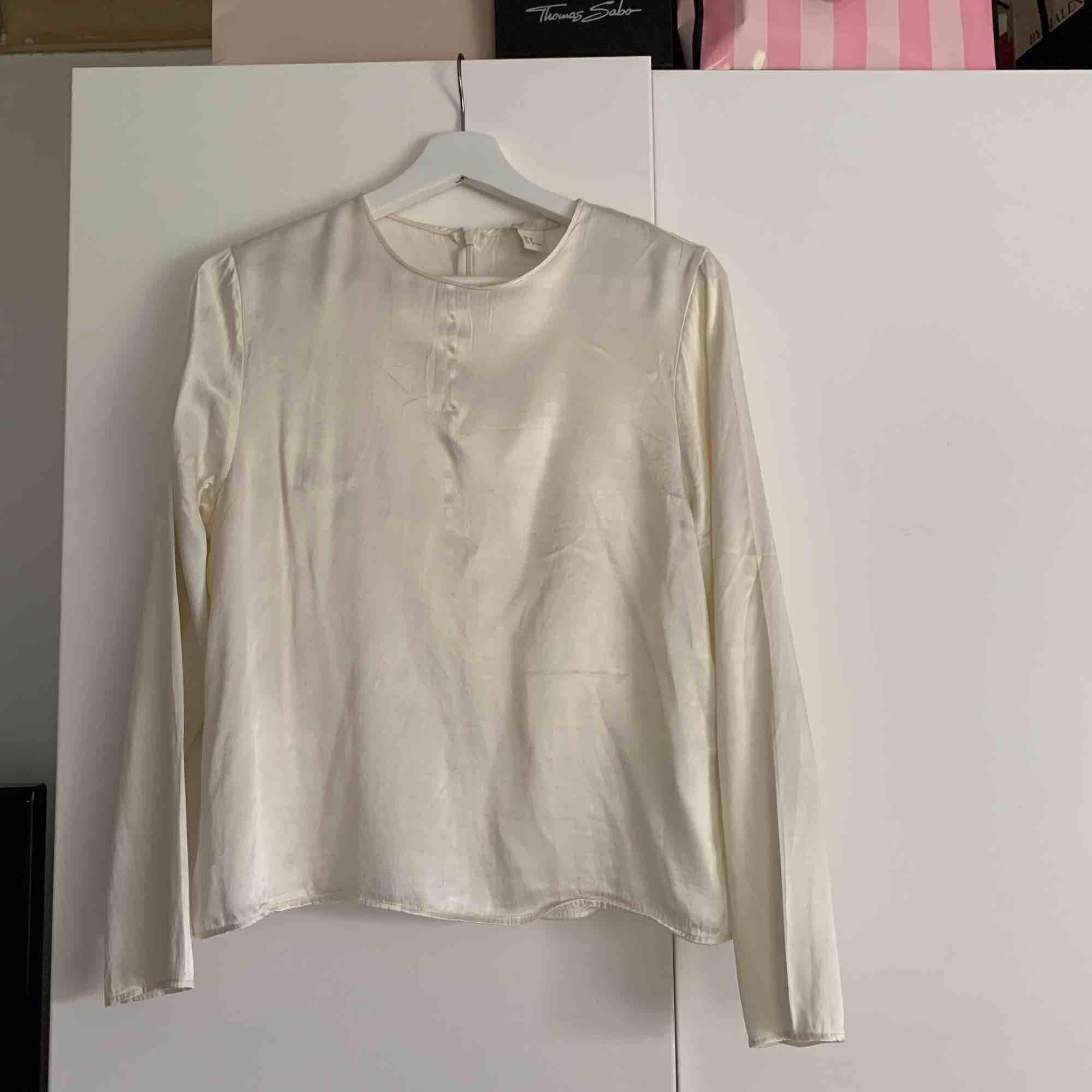 Säljer min vita blus från h&m. Som ni ser på bild två är det en sminkfläck vid halsen men det går säkert bort om man t.ex tar diskmedel eller galltvål. . Blusar.