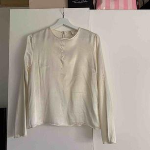 Säljer min vita blus från h&m. Som ni ser på bild två är det en sminkfläck vid halsen men det går säkert bort om man t.ex tar diskmedel eller galltvål.