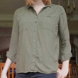 Militärgrön skjorta från HM. Längden passar någon under 170, jag är 182 därför ser den kort ut.