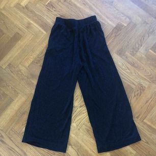 Mörkblå glittriga culottes-byxor.