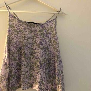 Ett blommigt linne med en snygg öppen rygg!! Frakten ingår😍