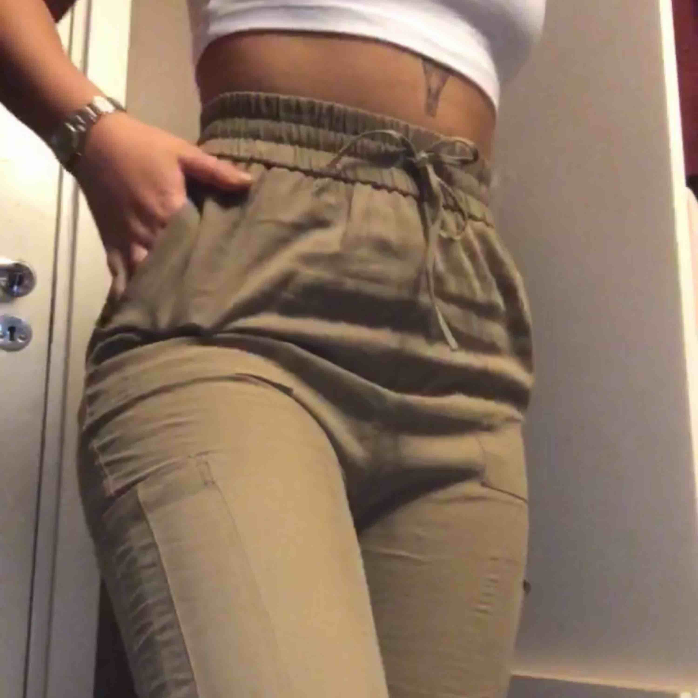 Högmidjade militärgröna chinos/byxor med fickor(korta i modellen). Är 160cm & de sitter lite över ankeln på mig. Snörning i midjan går inte att justera, är enbart detalj. Slittåligt material! Säljer på grund av de blivit för små.  Frakt ingår i priset. Jeans & Byxor.