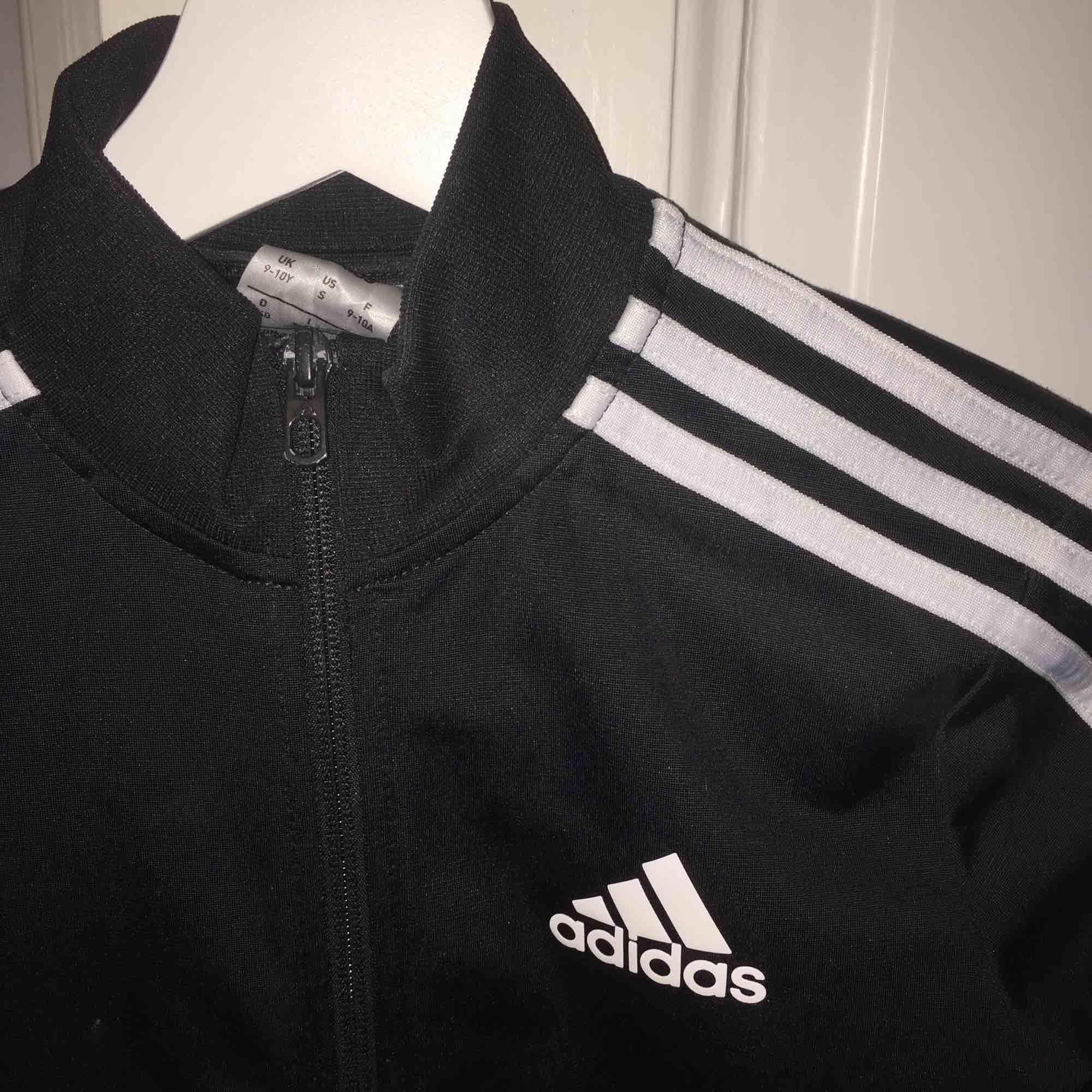 Adidas kofta i svart och vit, strl 140=XS, väl skick och saknar hål/fläckar. Huvtröjor & Träningströjor.