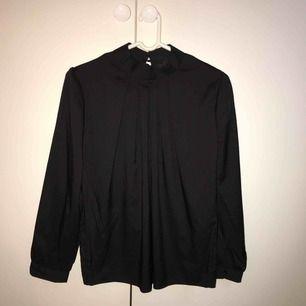 Svart skjorta med hög krage, storlek 36. Aldrig använd. Köparen står för frakt, kan mötas upp i Lund/Malmö