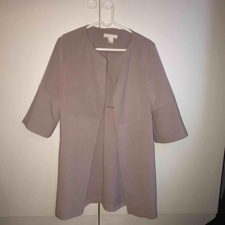 Ljus rosa/lila/beige pastell-aktig kappa med halva ärmar från h&m, storlek 34 men sitter väldigt löst så passar även 36. Bara använd ett par gånger. Köparen står för frakt, kan mötas upp i Lund/Malmö . Jackor.